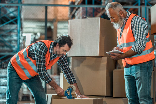 Men in warehouse filling boxes with product